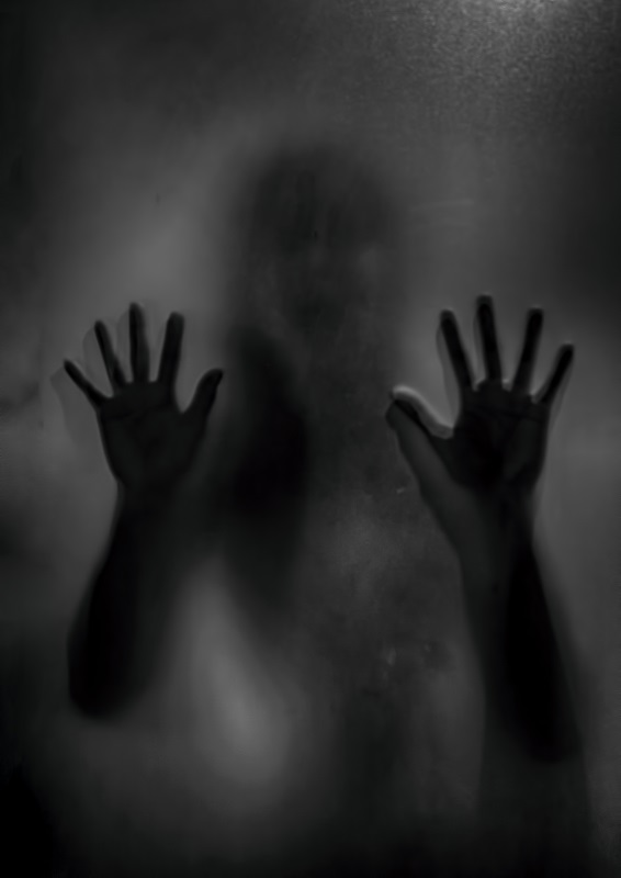 Horror ghost girl behind the matte glass in black and white. Halloween festival concept.